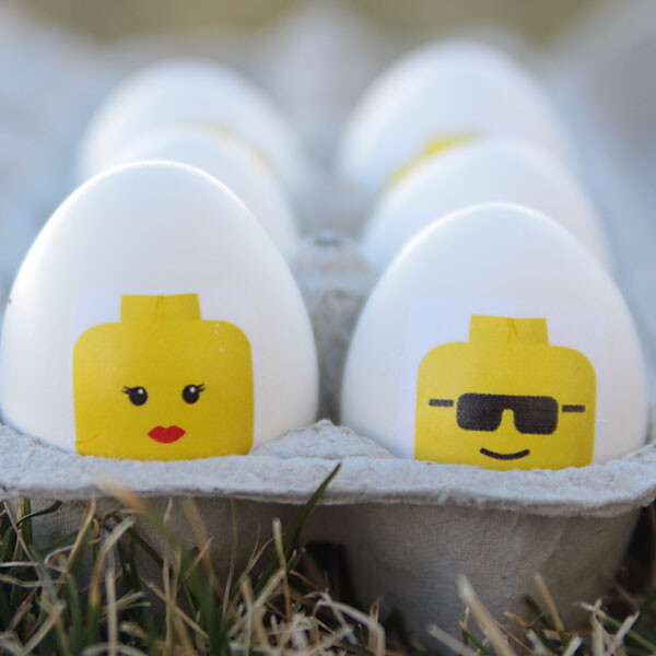 Easter eggs with lego minifig heads on them in a carton