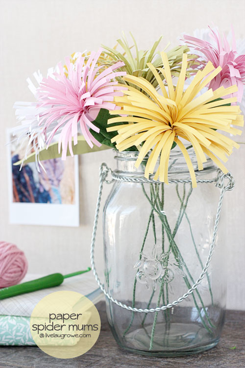 A vase of paper flowers on a table