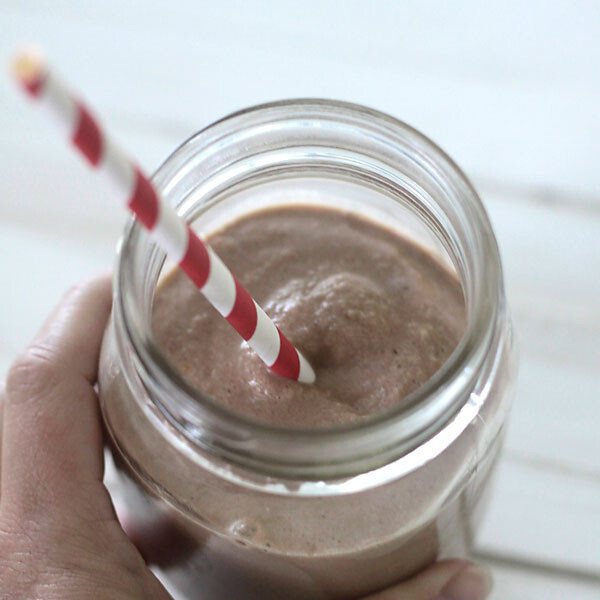chocolate peanut butter smoothie in a jar with a red and white straw