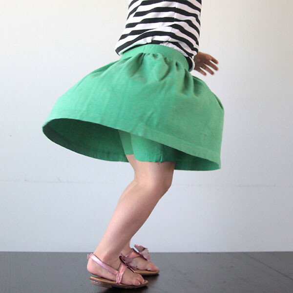 A young girl spinning around wearing shorts that have a skirt attached