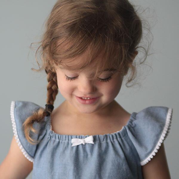 A little girl wearing a flutter sleeve sundress