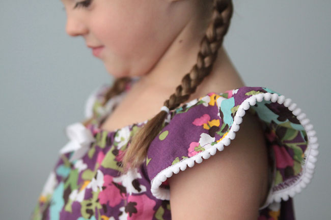 A close up of a girl wearing a purple shirt with pom pom trim on the sleeve