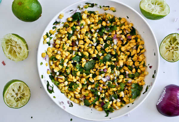 corn salsa in a bowl with limes around it