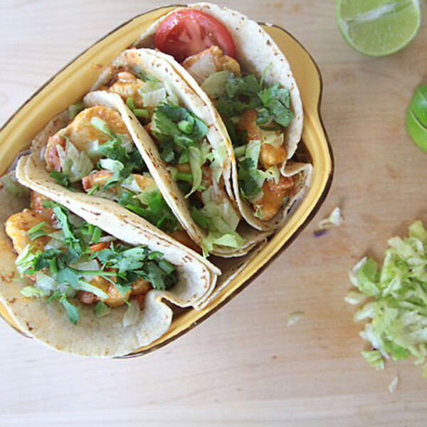 chicken tacos in a dish on a table with garnishes