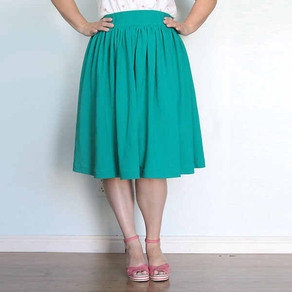 A woman wearing a full green gathered skirt with an elastic waist