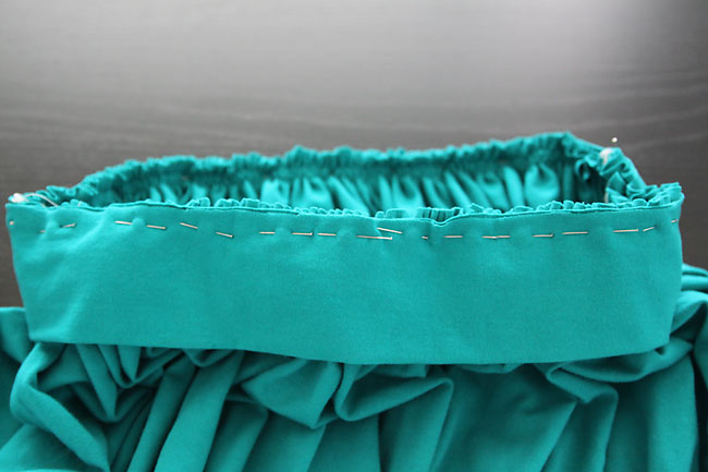 A close up of waistband pinned to a gathered skirt