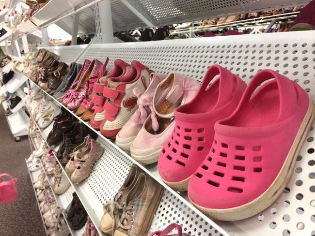 A rack of little girls shoes at a thrift store