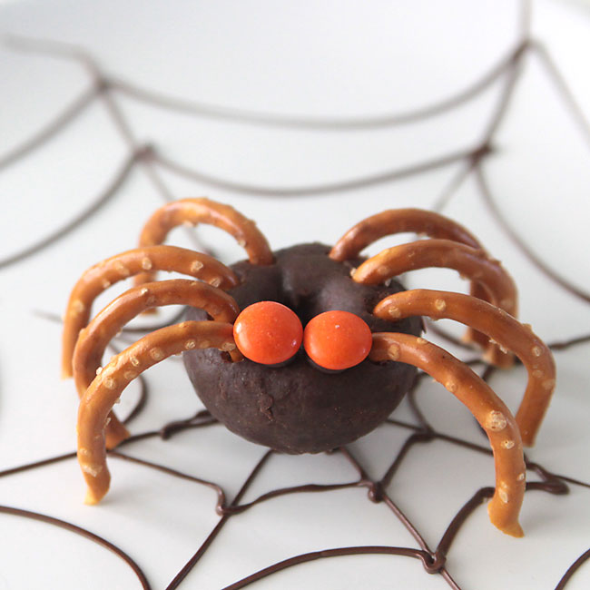 mini chocolate donut decorated to look like a spider with pretzel legs