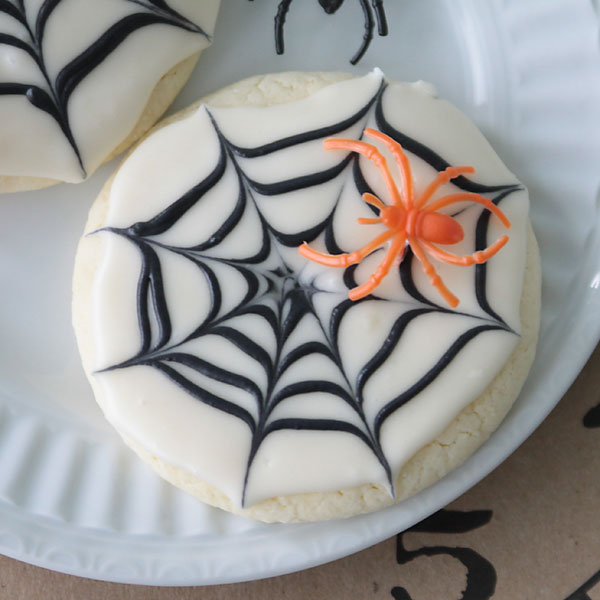 A sugar cookie with frosting that looks like a spiderweb and plastic orange spider on it
