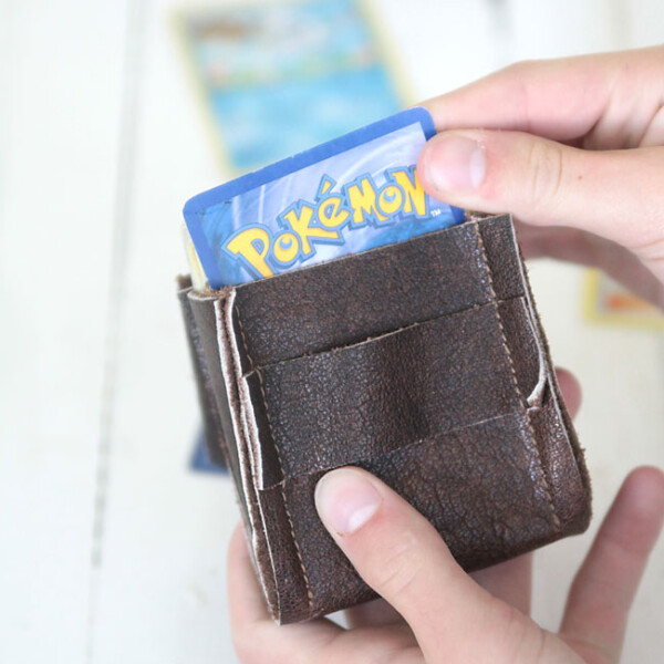 a boy holding a leather deck holder with pokemon cards in it