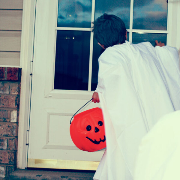 A little boy dressed as a ghost knocking on a door