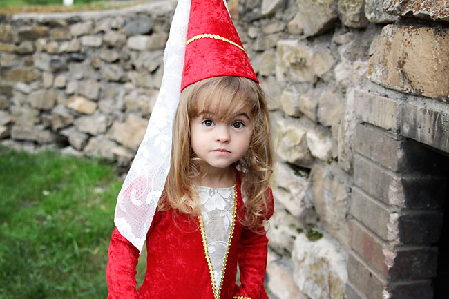 A little girl in a red princess costume in front of a stone wall