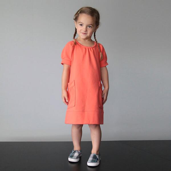 A little girl in an orange dress made from sweatshirt fabric