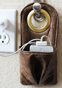 leather phone charger that hangs on a hook near an outlet with pocket for a phone