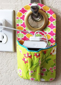 fabric phone charger that hangs on a hook near an outlet with pocket for a phone