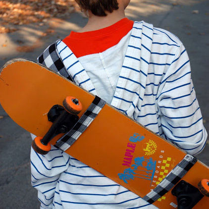 boy carrying a skateboard in a fabric sling