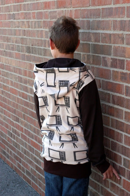 A boy standing in front of a brick building wearing a hooded sweatshirt