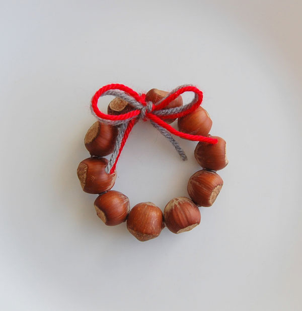 DIY Christmas ornament made from ring of acorns that looks like a wreath