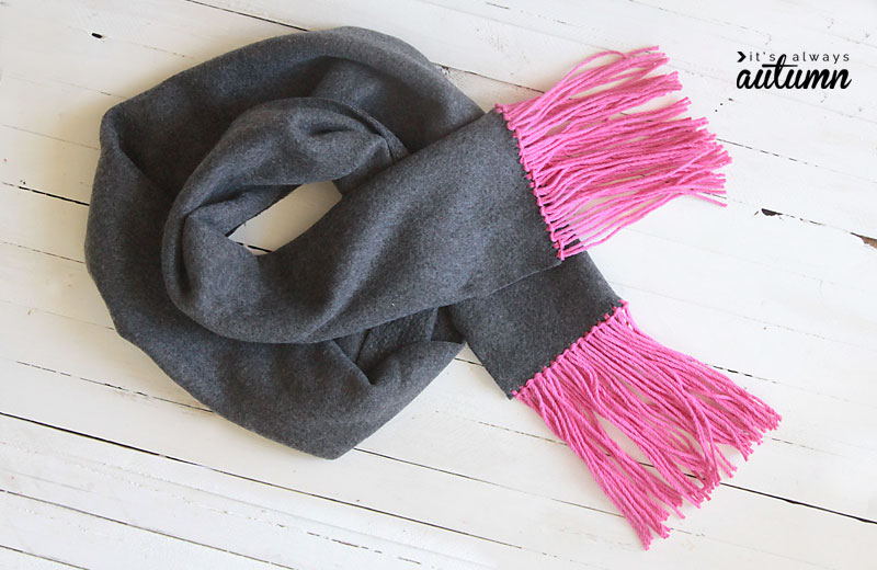 a fleece scarf with yarn fringe rolled up on a table