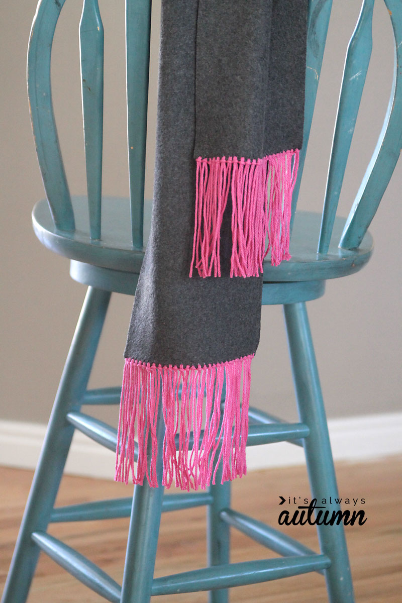 Scarf with yarn fringe hanging over a stool