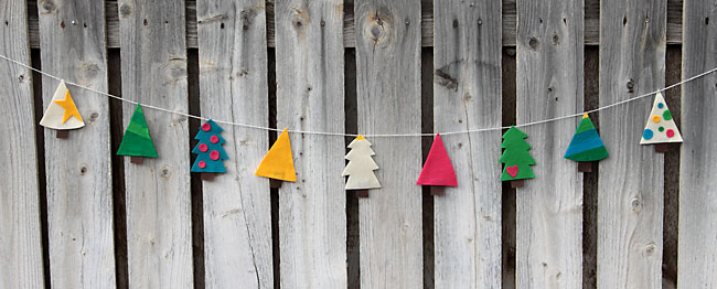 felt christmas tree garland hanging on a fence