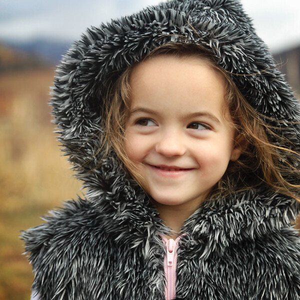 little girl wearing a hooded vest made from faux fur