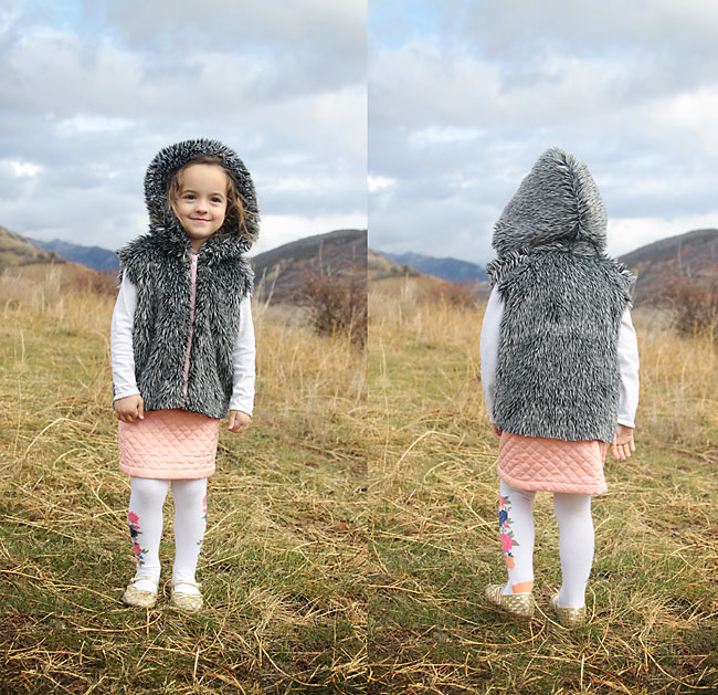 A little girl standing in a field wearing a faux fur vest with a hood