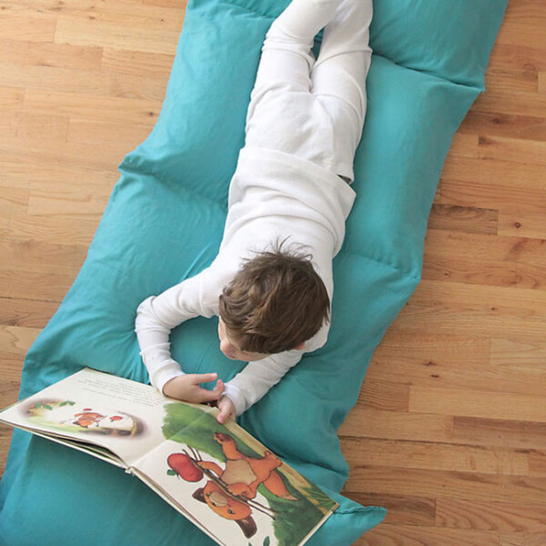 Boy laying on a pillow bed (portable mattress made from five pillows sewn together)