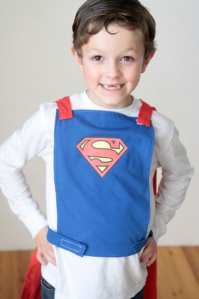 A little boy wearing a blue superhero cape