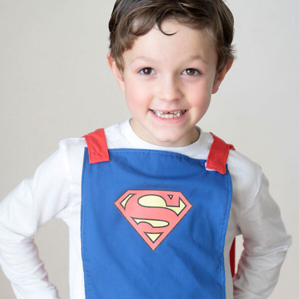 A little boy wearing a blue cape made with elastic so it will easily detach if pulled