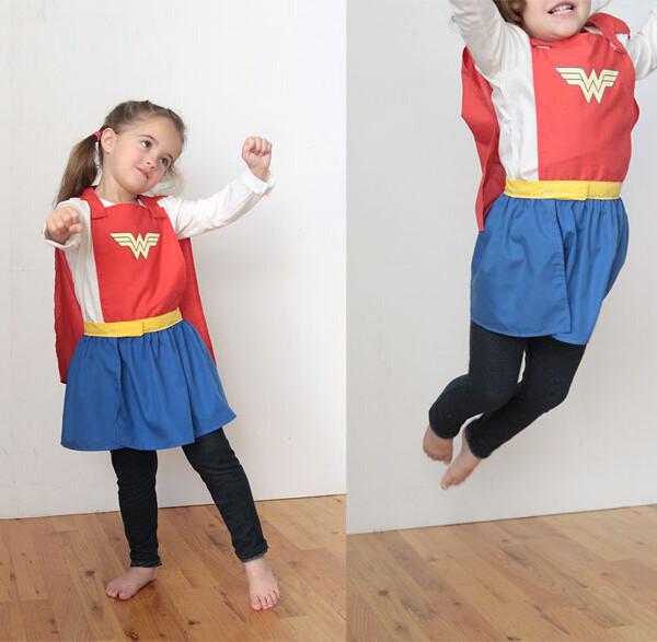 A little girl wearing a superhero cape and skirt