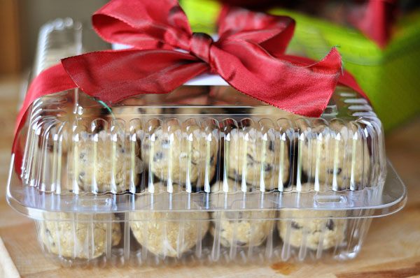 cookie dough balls in a plastic container with ribbon tied on top