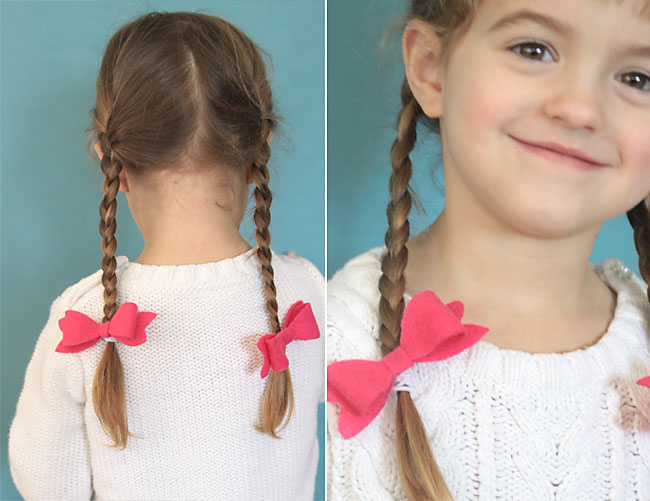 A little girl wearing pink hair bows at the end of her braids