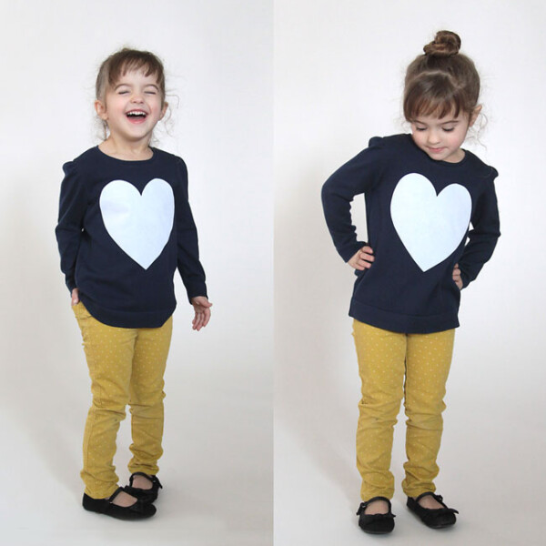 A girl wearing a blue sweater with a big white heart