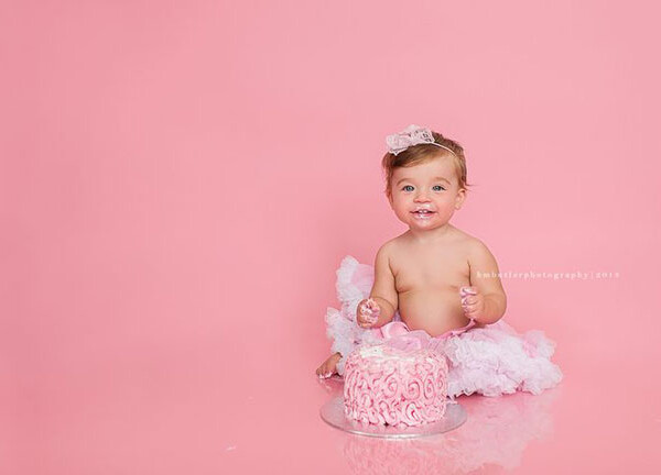 A little girl baby eating a cake with a pink background