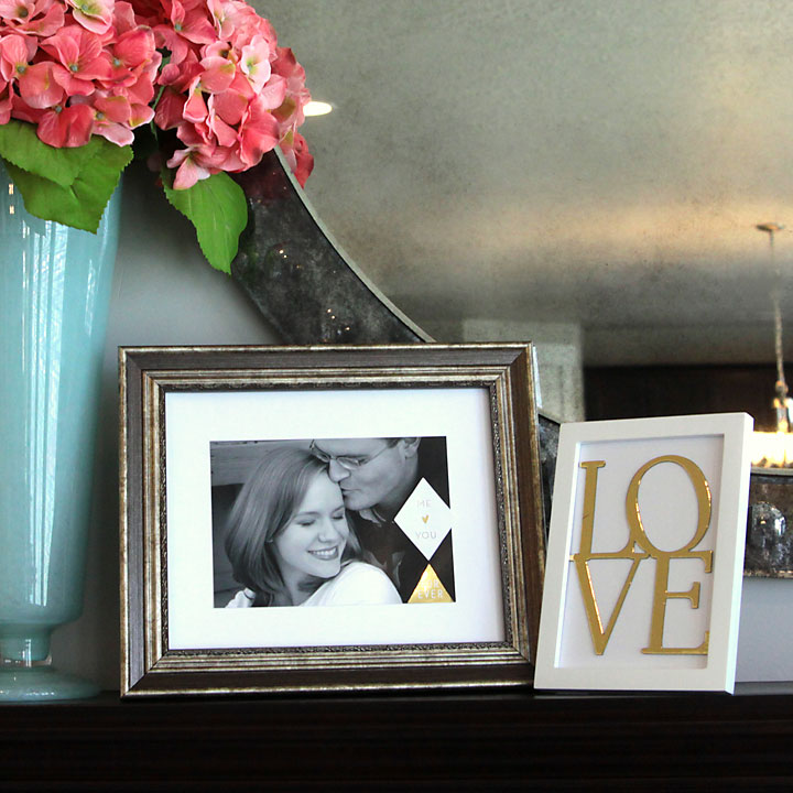 A framed photo of husband and wife; a framed sign that says LOVE in gold foil