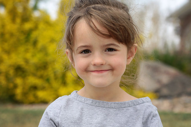 A little girl smiling at the camera with blurred yellow flowers in the background