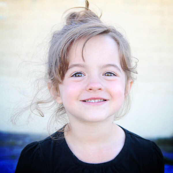 Little girl smiling at the camera in front of a brick wall that's blurred in the background