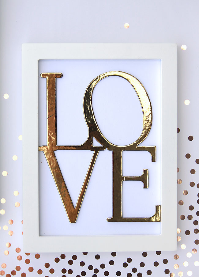 the Word LOVE with gold foil applied in a frame