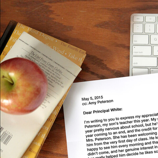 Letter to a principal next to books with an apple on top