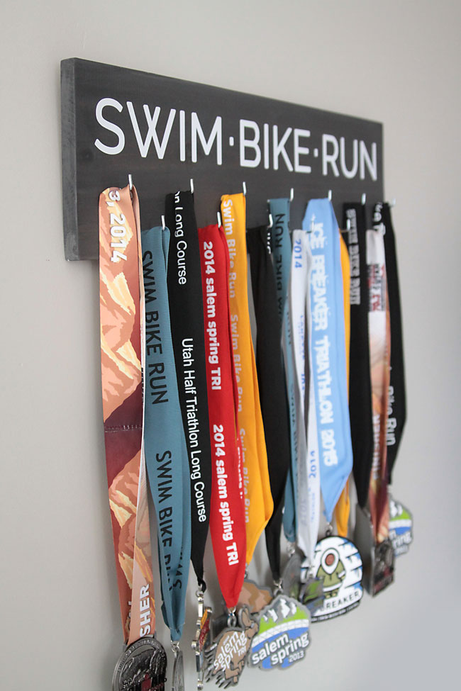 Sign that says swim bike run with race medals hanging from it