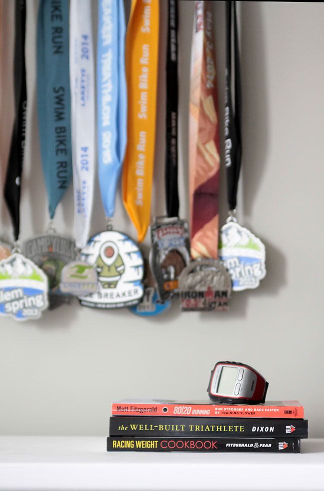 medals hanging on a wall, with books and watch