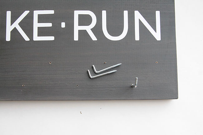 screwing hooks into holes drilled in sign