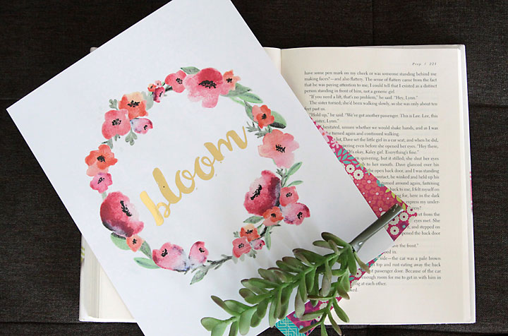 An art print with flowers and the word bloom laying on a book