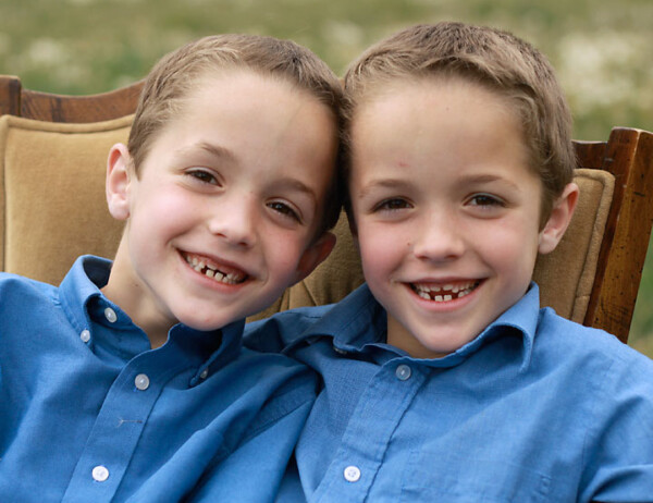 Two siblings sitting in a chair in a field smiling