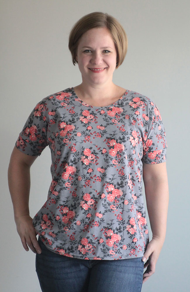 A woman wearing a grey floral shirt made from the breezy tee sewing pattern