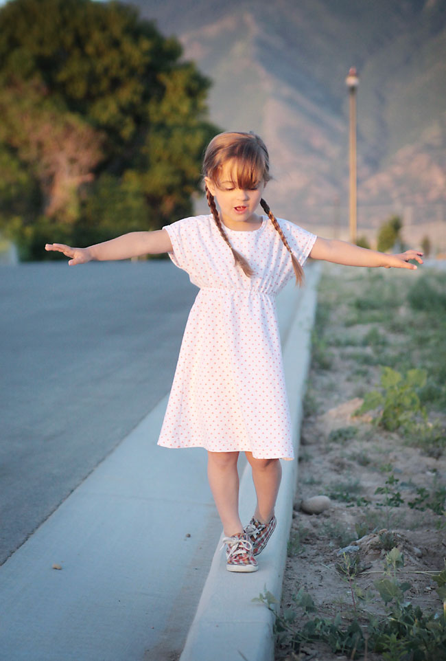 A young girl walking down the road in a play dress