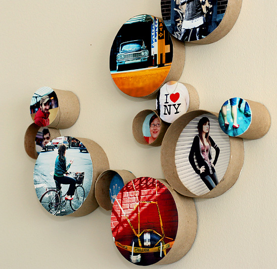 Circular photos framed with cardboard rolls hanging on a wall in a group