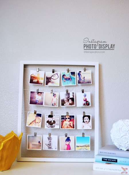 Frame with photos hanging from strings that go across the width of the frame