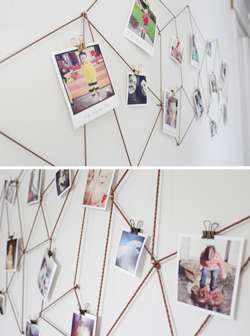 Photos hanging from string that\'s making geometric shapes on a wall